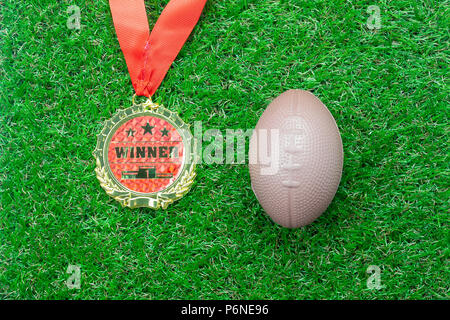 Table top view aerial image soccer or football season background.Flat lay accessories gold medal & american ball on the artificial green grass wallpap - Stock Photo