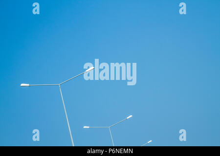 Street light poles against blue sky - Stock Photo