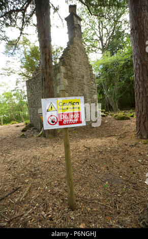 The remains of a stone cottage with ground cleared around it in woodland near Hawes Water lake in Silverdale with warning signs not to enter. Hawes Wa - Stock Photo