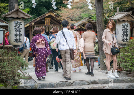 Japanese tourists explore Arashiyama in the outskirts of Kyoto, Japan. Arashiyama has been a popular destination since the 8th century. - Stock Photo
