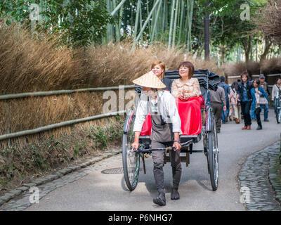 Traditional hand pulled rickshaw in Sagano Bamboo Forest in Arashiyama at the outskirts of Kyoto, Japan. - Stock Photo