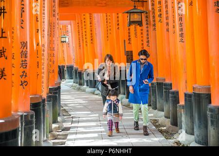 Japanese tourists explore Fushimi Inari Taisha in Kyoto, Japan. Along the main path there are more than 10000 torii gates. - Stock Photo