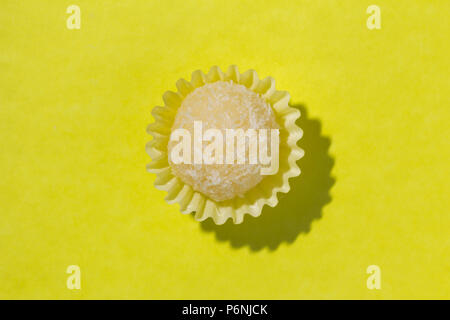 Beijinho is a handmade candy from Brazil. Made with condensed milk and coconut. Children brithday party sweet. Top view of candy on yellow background. - Stock Photo