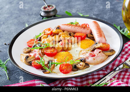 English breakfast - fried egg, beans, tomatoes, mushrooms, bacon and sausage. Tasty food. - Stock Photo
