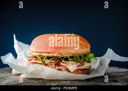 Homemade burger with chicken wrapped in paper on dark background - Stock Photo