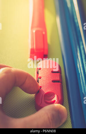 person enters code on the locking mechanism on the suitcase, access to personal belongings during the trip. The concept of tourism safety while travel - Stock Photo