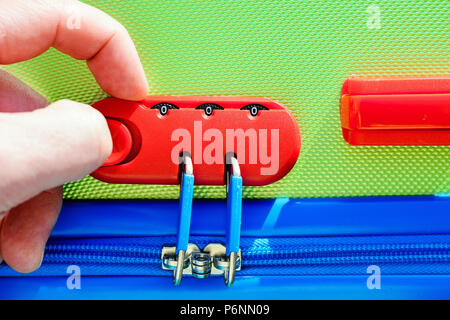 person opens a locking mechanism on the suitcase, access to personal belongings during the trip. The concept of tourist safety while traveling - Stock Photo