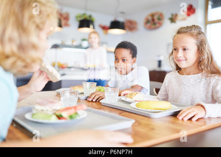 Happy pupils having lunch together in the canteen of elementary school - Stock Photo