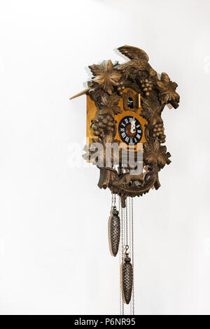 Old brown wooden cuckoo clock, on a white wall. - Stock Photo