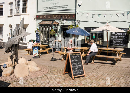 People sitting outside of Man of Ross Inn pub and enjoying drinks and sunny weather, Wye Street, The Man of Ross Inn, Ross on Wye, Herefordshire, UK - Stock Photo