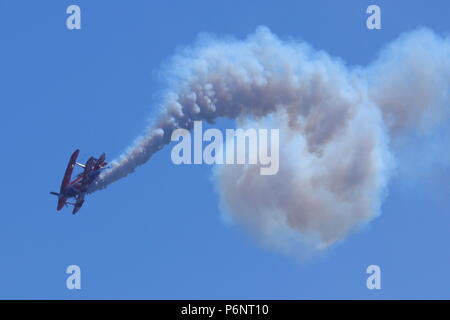 Rich Goodwin's Bi-plane performing acrobatic displays at Scarborough Armed Forces Day. - Stock Photo