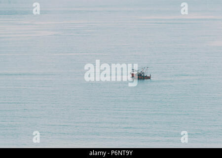 Abstract, minimal, surreal background - small boat sails quietly in sea water. Toned in soft cinematic colors in instagram style. - Stock Photo