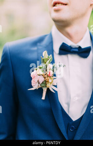 The boutonniere of roses on the jacket of the groom. - Stock Photo