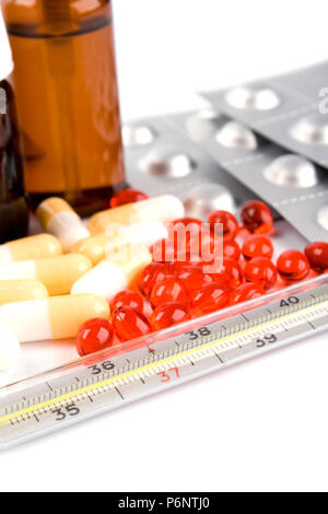 thermometer and different pills closeup on white background - Stock Photo
