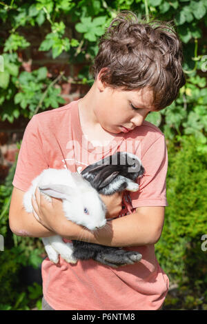 Boy hugging close little bunnies. Love portrait. Childhood and vacations with pets and animals. Polish countryside. - Stock Photo