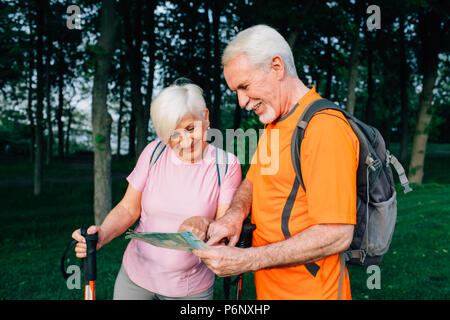 elderly couple hikers checking map in woods - Stock Photo