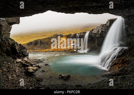 Low clouds hanging into Skutafoss on a rainy day. - Stock Photo