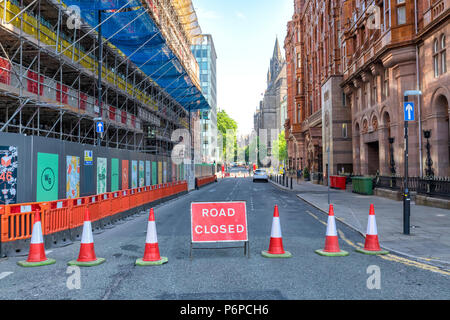 Cones and a Road Closed sign indicate a closed off road in Manchester city centre, UK. - Stock Photo