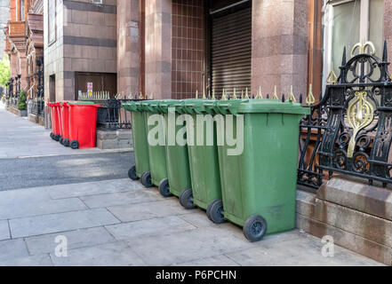 A row of 6 red and 5 green wheelie bins on the pavement in a street in Manchester City Centre, UK - Stock Photo