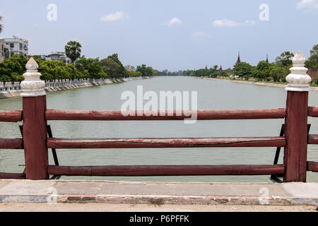 Wooden railings on the bridge over a canal at the Royal Palace in Mandalay, Myanmar. - Stock Photo