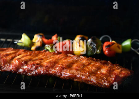 rack of barbecue spare ribs  cooking on a BBQ with green and red peppers, dark background for copy space - Stock Photo