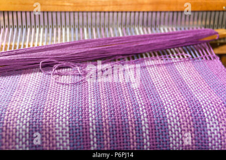detail of fabric in comb loom with ultraviolet and lilac colors - Stock Photo
