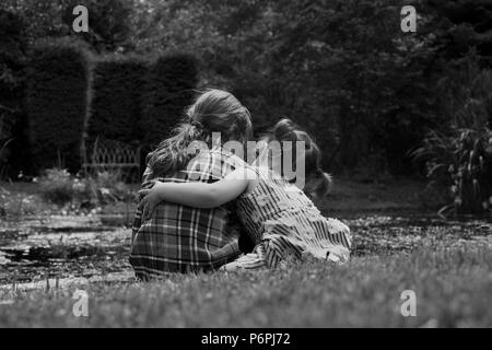 Little girl hugging her friend by a pond. - Stock Photo