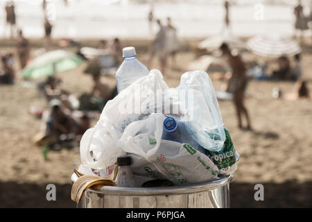 Overflowing litter bin full of plastic bottles and plastic bags on beach - Stock Photo
