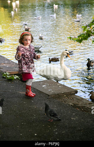 Young girl in red wellington boots playing in the park feeding the birds in Autumn, Dublin, Ireland, Europe. - Stock Photo