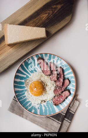Beautiful breakfast beef steak with pan-fried egg and some parmesan on top, top view, flat lay - Stock Photo