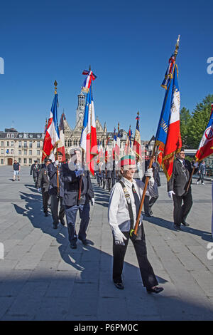 Men marching with raised banners and flags for Victory In Europe VE day 8th May 2018 in Place de l'Hotel de Ville St Quentin, Aisne, France. - Stock Photo