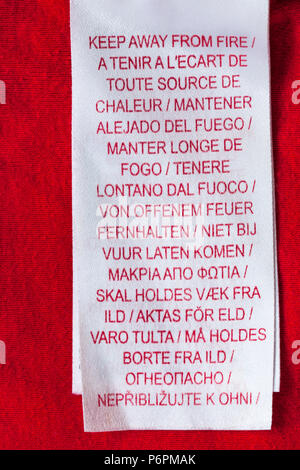 Keep away from fire label in many different languages  in clothing - Stock Photo