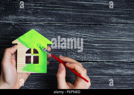 Man's hand paints the wooden house in the green brush. repair and renovation of the house, environmentally friendly house. Energy efficiency and quali - Stock Photo