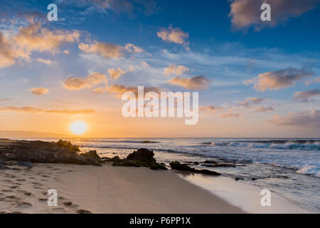 Sunset over Sunset Beach on the North Shore of Oahu, Hawaii with surf rolling in over coral rocks on the sandy beach - Stock Photo