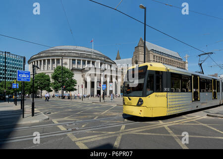 A Metrolink tram passes infront of the Central Library in St Peter's Sqaure in Manchester. - Stock Photo