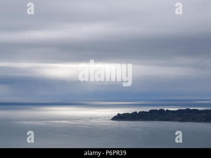 A thick layer of fog and clouds obscures the setting sun over the small coastal town of Bolinas in Marin County near San Francisco, California - Stock Photo