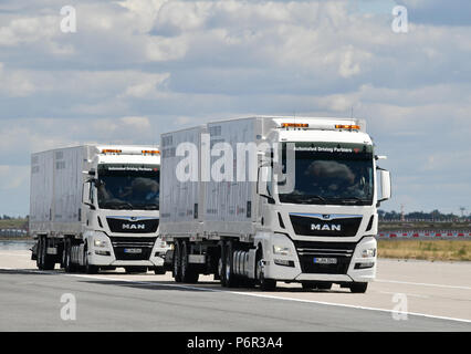 02 July 2018, Germany, Selchow: Trucks during a demonstration of platooning in autonomous driving in the unused south strip of Schoenefeld Airport. Platooning is convoy driving with very small distances between trucks through the aid of a technological driving system. DB Schenker, MAN Truck & Bus and the Fresenius University of Applied Sciences are for the first time testing truck platooning under actual driving conditions. In this test trucks are connected through a technological driver assistance and control system, as well as an electronic pivot line, in order to minimize the distance betwe - Stock Photo