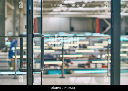 Open door in the modern office or shopping center with bokeh background - Stock Photo