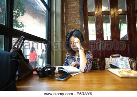 woman reading at banbangkhen cafe and garden,bangkok,thailand 13 may 2018 - Stock Photo