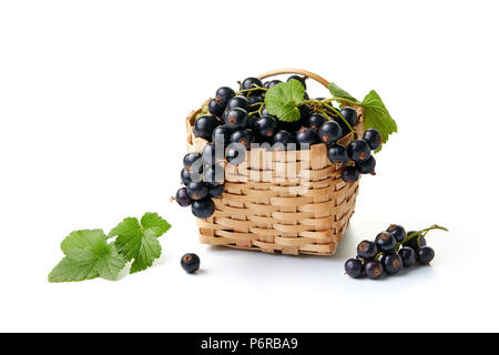 Blackcurrants in and beside a small wicker basket on white background. - Stock Photo