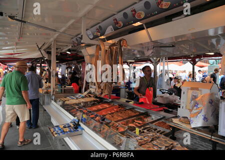 A stall sells fish and seafood products at the Fish Market (Fisketorget) in Bergen, Norway - Stock Photo