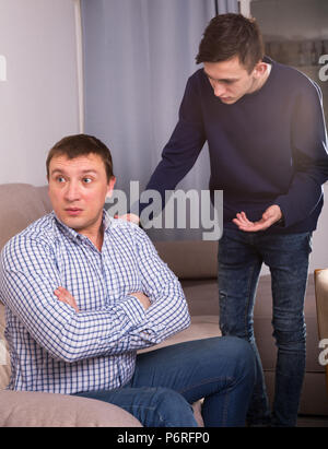 Man is offended and son is asking for his forgiveness at the home. - Stock Photo