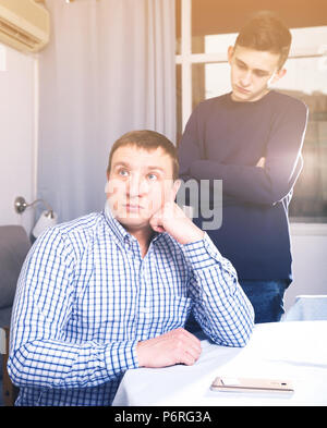Man is offended and son is not wanting talking with him at the home. - Stock Photo