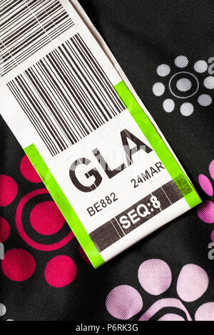 luggage label stuck on case for GLA Glasgow airport - Stock Photo