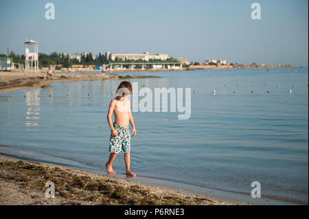 lonely handsome little kid in fashionable shorts walking along sea coast on summer beach - Stock Photo
