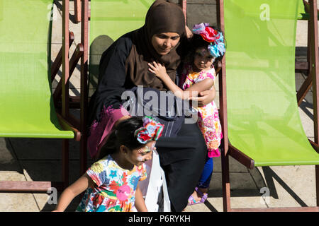 A young Muslim mother relaxes with her children in Lyric Square, Hammersmith, London, W6, UK - Stock Photo