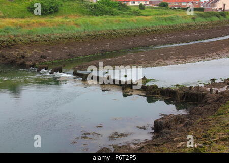 A broken water flow control dam crossing the river Avon at Aberavon in Port Talbot with slow water flow at low tide. - Stock Photo