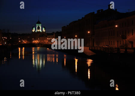 Lights of the Church of St. Isidor and Nicholas reflecting on the Griboyedov Canal in St. Petersburg, Russia, during night - Stock Photo