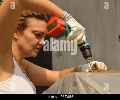Young beautiful woman in gloves uses drill in her garden. - Stock Photo