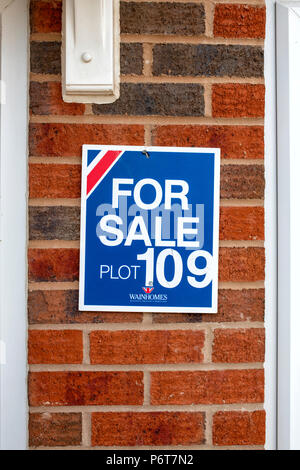 For Sale sign on the wall of a newly constructed house - Stock Photo